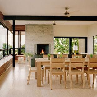 Immagine di una sala da pranzo aperta verso il soggiorno moderna con cornice del camino in cemento