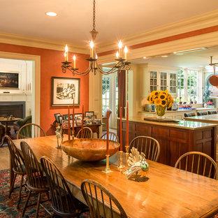 Idée de décoration pour une salle à manger ouverte sur la cuisine tradition avec un sol en bois brun, aucune cheminée et un mur orange.