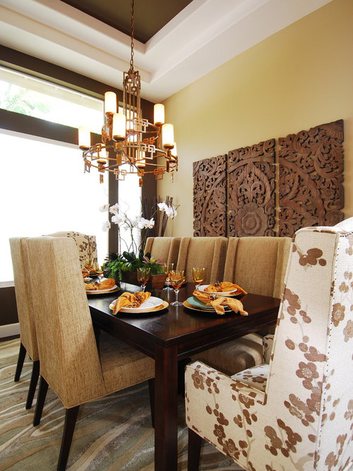 transitional dining room idea with yellow walls and carpet