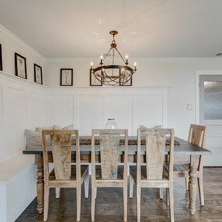 Foto di una grande sala da pranzo aperta verso la cucina country con pareti bianche, pavimento in legno massello medio, camino ad angolo, cornice del camino in mattoni e pavimento marrone