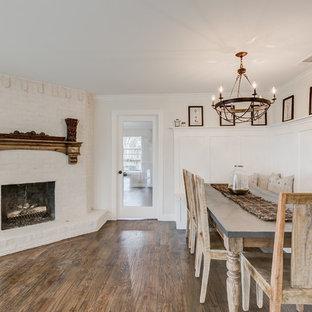 Foto de comedor de cocina de estilo de casa de campo, grande, con paredes blancas, suelo de madera en tonos medios, chimenea de esquina, marco de chimenea de ladrillo y suelo marrón