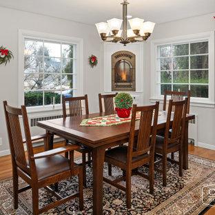 Источник вдохновения для домашнего уюта: кухня-столовая в классическом стиле с серыми стенами, паркетным полом среднего тона, угловым камином, фасадом камина из вагонки и коричневым полом