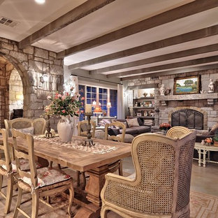 Ispirazione per un'ampia sala da pranzo aperta verso il soggiorno stile shabby con pavimento in cemento e cornice del camino in pietra