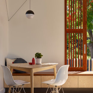 Small contemporary dining room in Brisbane with white walls, light hardwood floors and brown floor.