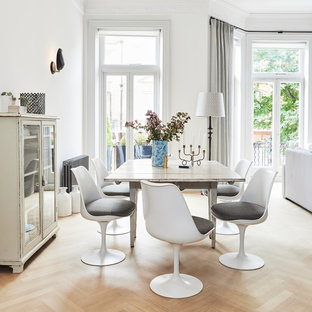Scandi dining room in London with white walls, light hardwood flooring and beige floors.