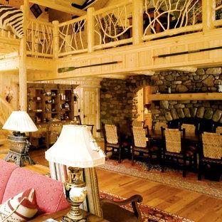 Modelo de comedor rural, grande, abierto, con paredes marrones, suelo de madera en tonos medios, chimenea de doble cara y suelo azul