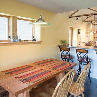 Immagine di una piccola sala da pranzo aperta verso la cucina stile rurale con pareti gialle, pavimento in cemento, nessun camino e pavimento grigio