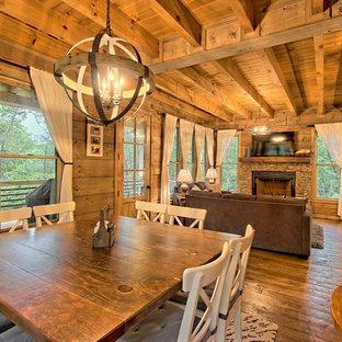 Rustik inredning av en liten matplats med öppen planlösning, med grå väggar, målat trägolv, en standard öppen spis, en spiselkrans i sten och brunt golv