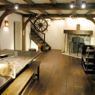 На фото: кухня-столовая в стиле рустика с темным паркетным полом и угловым камином с