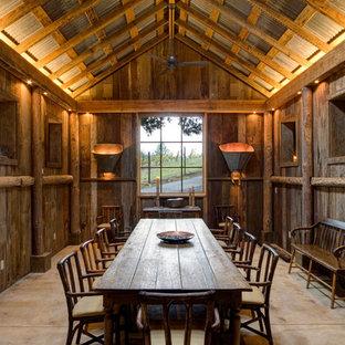 Стильный дизайн: отдельная столовая в стиле рустика с коричневыми стенами и бетонным полом - последний тренд