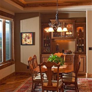 Imagen de comedor rústico, grande, abierto, con paredes beige, suelo de madera en tonos medios, chimenea tradicional y marco de chimenea de piedra