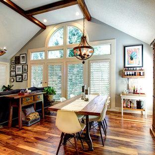 Imagen de comedor rural, grande, con paredes grises, suelo de madera en tonos medios, chimenea de doble cara y marco de chimenea de baldosas y/o azulejos