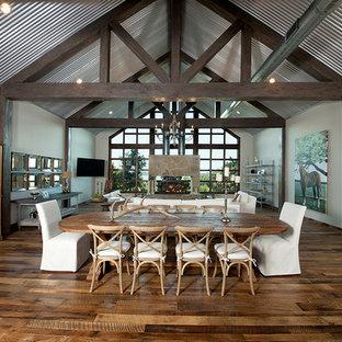 Imagen de comedor rústico, extra grande, abierto, con paredes blancas, suelo de madera oscura, chimenea de doble cara, marco de chimenea de piedra y suelo marrón
