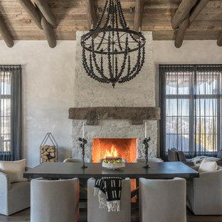 Imagen de comedor rural con paredes blancas, suelo de madera en tonos medios, chimenea tradicional, suelo marrón y marco de chimenea de piedra