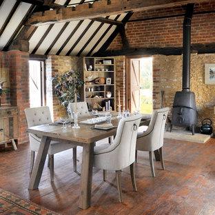 Foto di una sala da pranzo country con pavimento in legno massello medio e stufa a legna