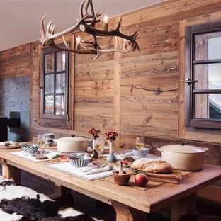 Idées déco pour une salle à manger ouverte sur le salon montagne de taille moyenne avec un mur marron et un sol en bois brun.