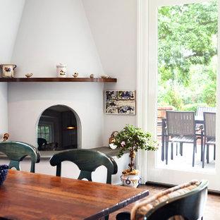 Réalisation d'une salle à manger ouverte sur la cuisine tradition de taille moyenne avec un sol en bois brun, une cheminée d'angle, un mur gris, un manteau de cheminée en plâtre et un sol marron.