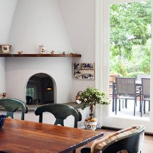 Modelo de comedor de cocina clásico renovado, de tamaño medio, con paredes grises, suelo de madera en tonos medios, chimenea de esquina, marco de chimenea de yeso y suelo marrón
