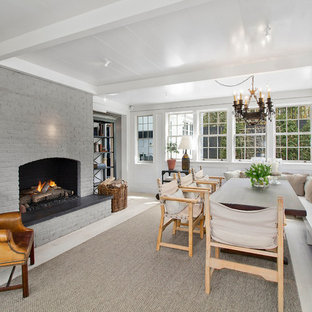 Example of a transitional enclosed dining room design in New York with white walls, a standard fireplace and a brick fireplace