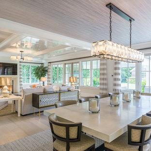 Diseño de comedor clásico, grande, abierto, con paredes blancas, suelo de madera clara, chimenea tradicional, marco de chimenea de hormigón y suelo beige