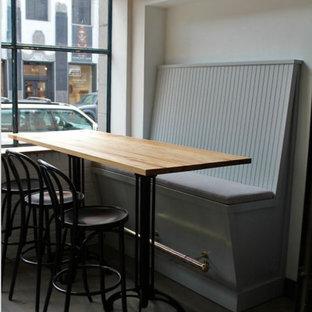 Idee per una sala da pranzo aperta verso il soggiorno industriale di medie dimensioni con pareti bianche, parquet scuro, camino sospeso e pavimento nero