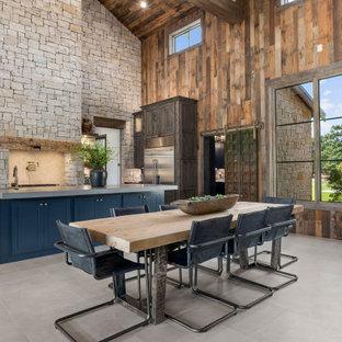 Lantlig inredning av en matplats med öppen planlösning, med bruna väggar och grått golv