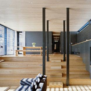 Exemple d'une grand salle à manger ouverte sur la cuisine scandinave avec un mur noir, un sol en bois clair et aucune cheminée.
