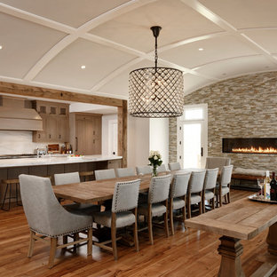 Modelo de comedor de cocina rural con paredes blancas, suelo de madera en tonos medios, chimenea lineal, marco de chimenea de baldosas y/o azulejos y suelo marrón