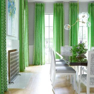 Idee per una sala da pranzo chic con pareti grigie, parquet chiaro e camino classico