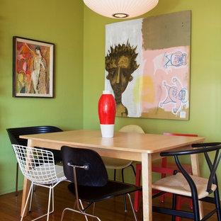 Foto de comedor ecléctico con paredes verdes y suelo de madera oscura