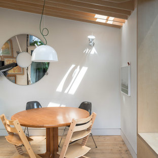 Photo of a medium sized scandinavian dining room in London with white walls, light hardwood flooring and beige floors.
