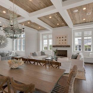 Ejemplo de comedor de cocina rural, de tamaño medio, con paredes blancas, suelo de madera en tonos medios, chimenea tradicional, marco de chimenea de yeso y suelo beige