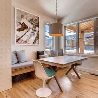 Diseño de comedor minimalista, pequeño, abierto, con paredes blancas, suelo de madera clara, chimenea tradicional, marco de chimenea de baldosas y/o azulejos y suelo blanco