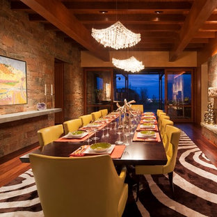 Example of a huge southwest medium tone wood floor and brown floor enclosed dining room design in Albuquerque with a standard fireplace, multicolored walls and a stone fireplace