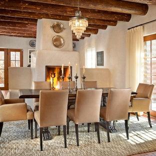Cette photo montre une salle à manger sud-ouest américain avec un mur beige, un sol en brique, un manteau de cheminée en plâtre et une cheminée standard.