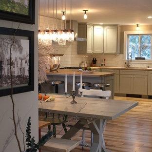 Modelo de comedor de cocina de estilo de casa de campo, pequeño, con paredes grises, suelo de madera en tonos medios, chimenea de doble cara, marco de chimenea de yeso y suelo marrón