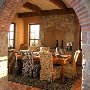 Aménagement d'une salle à manger montagne avec un mur orange, une cheminée standard, un manteau de cheminée en pierre et un sol en carreau de terre cuite.