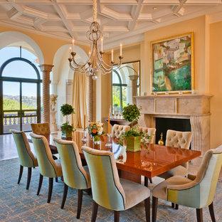Imagen de comedor clásico, extra grande, cerrado, con paredes amarillas, suelo de mármol, chimenea tradicional, marco de chimenea de piedra y suelo marrón