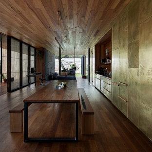 Foto di una sala da pranzo aperta verso la cucina minimalista con pareti con effetto metallico e parquet scuro