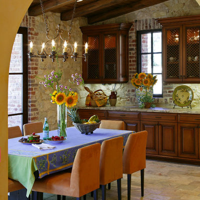 Example of a mid-sized tuscan limestone floor and beige floor kitchen/dining room combo design in Orange County with no fireplace and beige walls