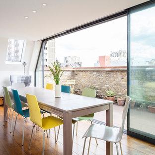 Exempel på en mellanstor minimalistisk matplats med öppen planlösning, med vita väggar och mellanmörkt trägolv