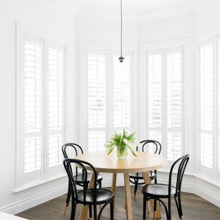 Exemple d'une petite salle à manger ouverte sur la cuisine scandinave avec un mur blanc et un sol en bois brun.