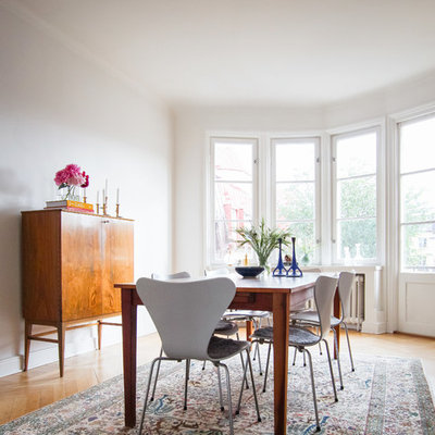 Example of a mid-sized danish medium tone wood floor dining room design in San Francisco with white walls