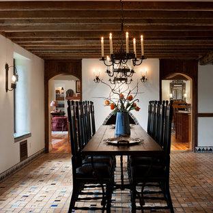 Immagine di una grande sala da pranzo aperta verso la cucina classica con pareti bianche, camino classico, cornice del camino piastrellata e pavimento in mattoni