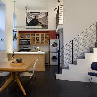 Idee per una piccola sala da pranzo aperta verso il soggiorno industriale con pareti bianche, pavimento nero, parquet scuro e nessun camino