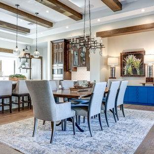 Foto di una grande sala da pranzo aperta verso la cucina design con pareti bianche, pavimento in legno massello medio, camino ad angolo, cornice del camino in pietra e pavimento marrone