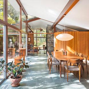 На фото: большая гостиная-столовая в стиле ретро с полом из сланца и коричневыми стенами с