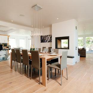 Esempio di un'ampia sala da pranzo aperta verso la cucina minimal con pareti bianche, pavimento in legno massello medio, stufa a legna e cornice del camino in intonaco