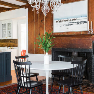 Example of a coastal dining room design in Boston with a wood stove
