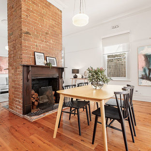 Inspiration for a transitional dining room in Melbourne with white walls, medium hardwood floors and brown floor.